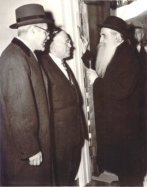 Rav Binyomin Teitz affixes the mezuzah for the dedication of Adath Israel